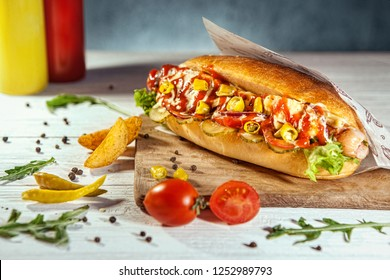 Hot tasty hot dog with jalapeno in craft envelope on white wooden table, near by french fries, arugula and cherry tomato.