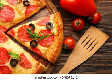 Hot tasty pizza with salami and olives on wooden background, close up