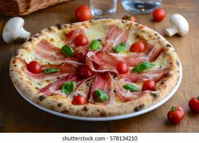 Hot tasty pizza from wooden oven with prosciutto, mozzarella, cherry tomatoes and basil, served for a dinner in italian restaurant. Italy food.