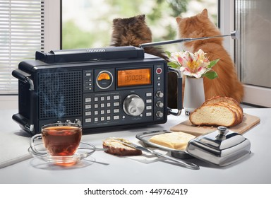 Hot tea, bread and oil on a table with the radio receiver against an open window