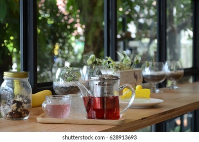 Hot tea and cake with interior coffee shop garden background.