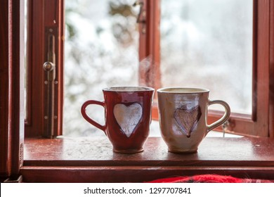 hot tea in ceramic cps with hearts on wooden window pane