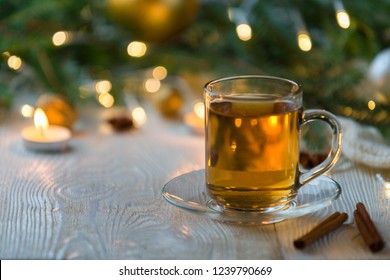 Hot tea in Christmas in a glass transparent Cup with tea, Christmas tree and candels.