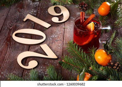 Hot tea with cinnamon and tangerines on wooden background. The concept of New year or Christmas. 2019. Figures from wood.