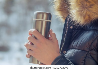 hot tea or coffee out of thermos in woman hands  on winter forest background. girl using a thermos in on a snowy mountain.