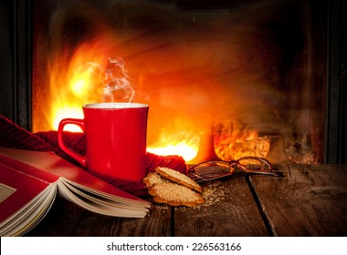 Hot tea or coffee in a red mug, ginger cookies, book and glasses on vintage wood table. Fireplace as background. Christmas or winter warming drink. Layout with free text space.
