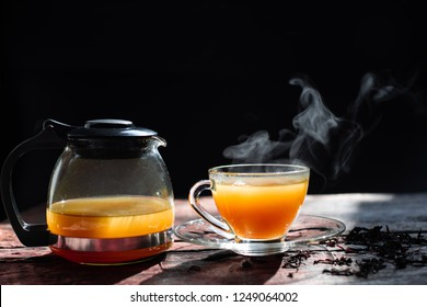 Hot tea cup in a glass on wood background.Hot drink . Copy space.