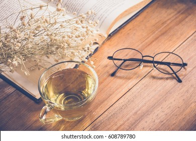 Hot tea in a cup with old book and flower on table