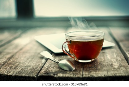 Photo of Hot tea cup on a frosty winter day window background