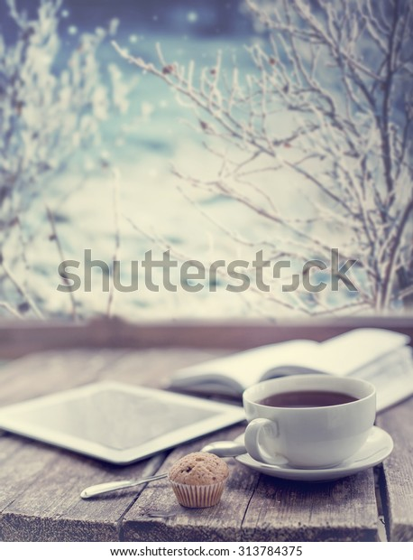 Hot tea cup on a frosty winter day window background/ Christmas holidays background/ Winter cozy background