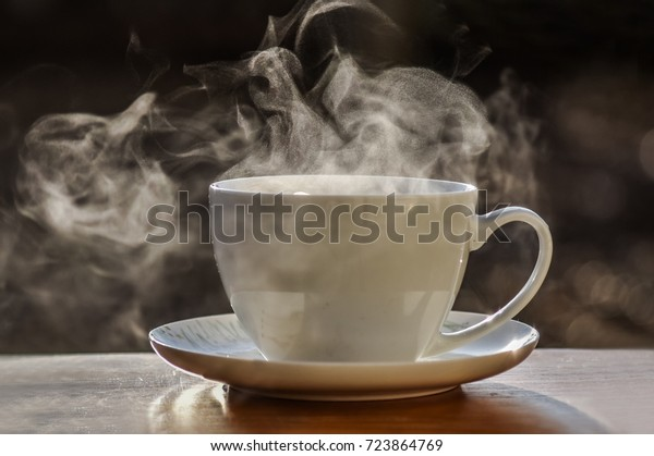 Hot tea cup on a frosty winter day put on wooden table with background of front garden in morning.