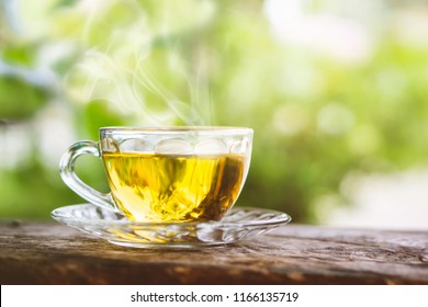 hot tea cup on wooden table with background of nature sunlight in the morning