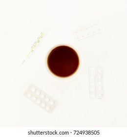 Hot tea cup with pills and thermometer on white background. Flat lay, top view. Medical concept