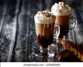 Hot tea decorated with whipped cream dripping and chocolate sprinkles inside vintage glasses served with salted caramel biscotti.