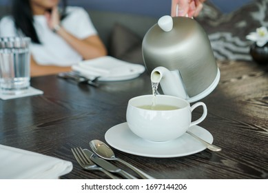 Hot tea drink. Pouring hot tea from tea pot to a white cup on the table, afternoon tea time.