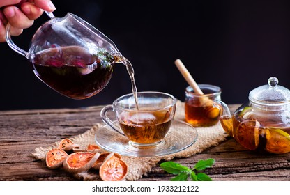 Hot tea in glass teapot and cup with steam on wooden table, black background