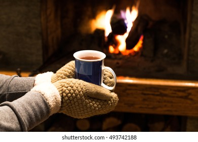 Hot tea in hands and fireplace