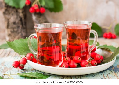 Hot tea from hawthorn berries in transparent glasses on a wooden table