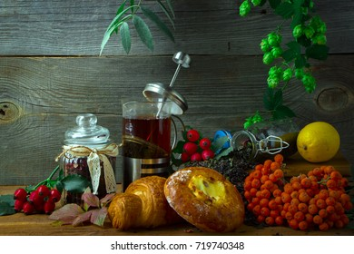 Hot tea jug on a wooden background surrounded by autumn fruits and baked goods