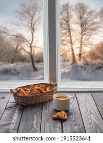 Hot tea with lemon and cookies by the window against the background of winter  trees at sunset. Home comfort concept.