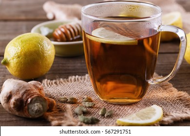 Hot tea with lemon, ginger and cardamom over rustic wooden background close up