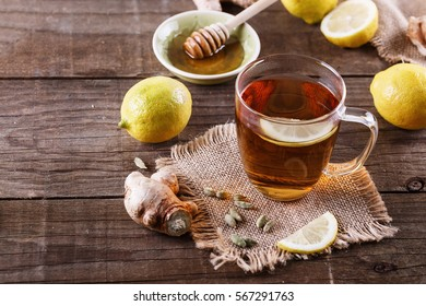 Hot tea with lemon, ginger, honey and cardamom over rustic wooden background close up