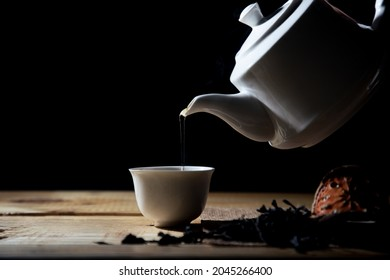 Hot tea is pouring from a teapot into a white cup with herbs on a black background