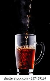 Hot tea pours into a transparent mug on a black background