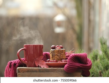 Hot tea in a red ceramic mug,chocolate cake with cherries in a rustic garden