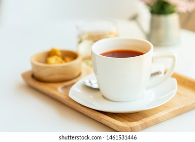 Hot tea with snacks on wooden tray. Set of drinks.