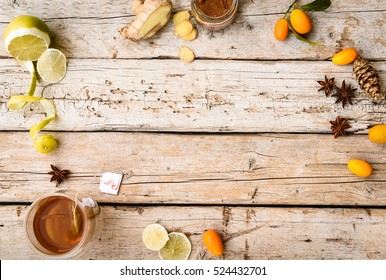 Hot tea, spices, lemon, oranges, cone and ginger root on a wooden background. Winter still life. Up view. Copy space for your text.