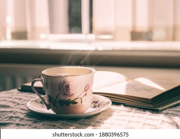 Hot tea with steaming in cinematic tone, Still life cuppa tea with steam on a coffee table with morning light shining from window, Cozy scene of relaxing in afternoon in tearoom