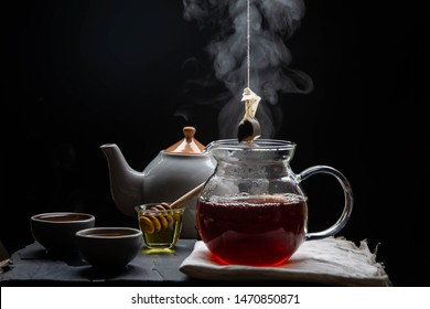 Hot tea in a teapot and teacup with steam and tea filter bags on revive the wood and black backdrop.