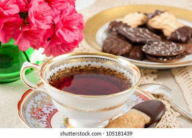 Hot tea in a vintage teacup on a lace tablecloth accented with cookies and bright pink Azaleas