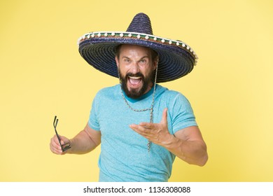 Hot tempered people. Man shouting face in sombrero hat yellow background. Guy with beard looks annoyed or angry in sombrero. Traditional rules of behaviour and manners. Man annoyed behaviour shout.