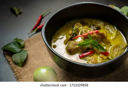 Hot Thai chicken green curry or Kiew Wan curry on table with spices & herbs.  Thai Chicken green curry is a tasty traditional Thai food made from coconut milk & green curry paste. Thai food concept.