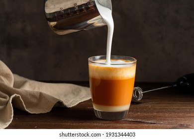 Hot Thai tea latte with milk froth in the glass. Pouring milk froth to the glass.