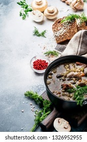 Hot thick mushroom soup with beef, spices and wholegrain barley, meat broth. With black bread, in metal pan, top view, flat lay, gray kitchen table backgound