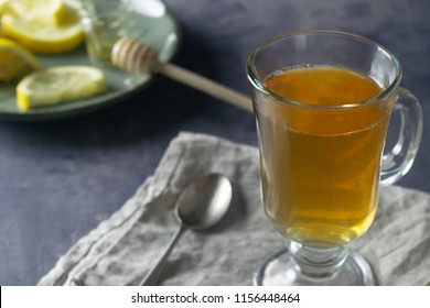 Hot Toddy Cocktail In Irish Coffee Glass with Lemon and Wooden Honey Spoon On Dark Background.