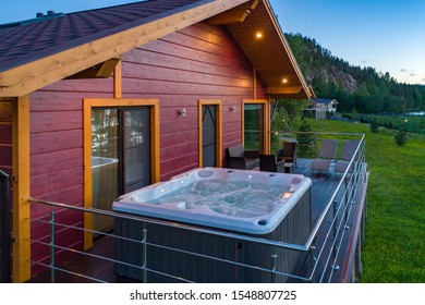 Hot tub at the house's balkon. Country cottage. Swimming pool for spa treatments in a private house. The hydromassage pool on a terrace. Penthouse overlooking the northern forest. Northern nature.
