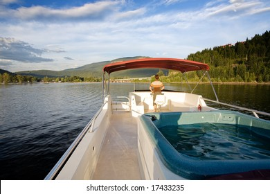 A hot tub on a luxury boat on a lake at sundown