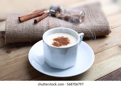 Hot Turkish Salep with cinnamon sticks on wood bacground