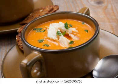 Hot two bowls of crab bisque garnished with fresh cooked Dungeness crab meat and green chives. Garnished with whole grain crackers. Rustic style.