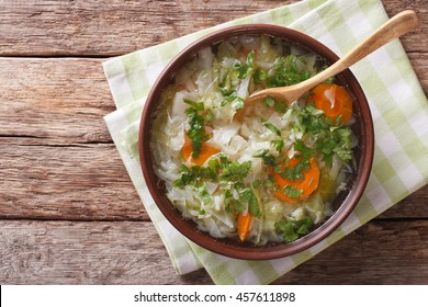 Hot vegetable soup with cabbage close up in a bowl on the table. horizontal view from above