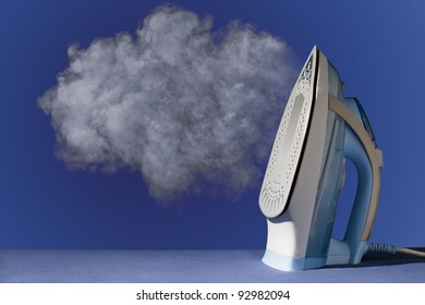 hot vertical new iron throws cloud of white steam on blue background