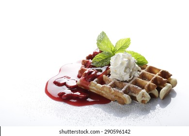 hot waffle topped with hot cherries and whipped cream