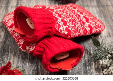 Hot water bottle on the background. Red bag with water on wooden table