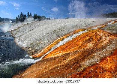 Hot water from the Midway Geyser Basin cascades into the Firehole River in Yellowstone National Park - Wyoming