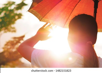 Hot weather can cause dehydration and sunstroke The girl is holding an umbrella and raising her hand. To block the hot sunlight.