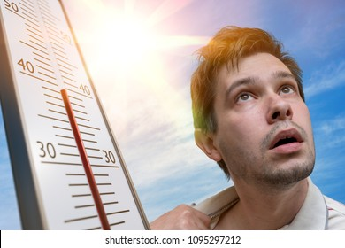Hot weather concept. Young man is sweating. Thermometer is showing high temperature. Sun in background.